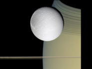 This image may seem like some kind of artist's rendering, but it's an actual true-color photograph showing Saturn, its rings, and one of its moons, Dione.