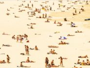 An image of people on the beach illustrating how researchers can tan human skin without UV exposure.