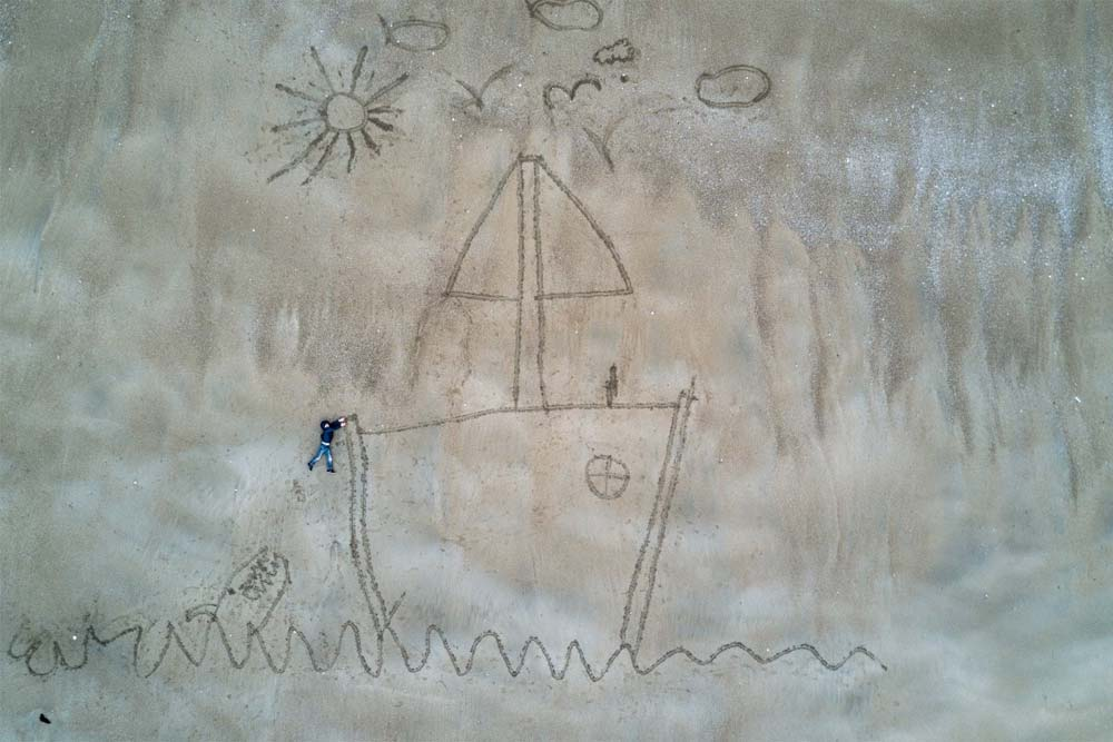 sand drawing of child is hanging from the bow of a ship